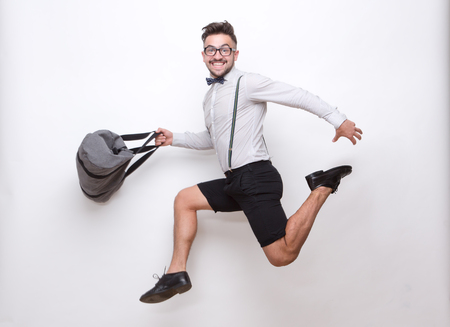 imagining: Hipster man jumping with a bag in his hands in photo studio. Happy man imagining that he is running somewhere over white background.
