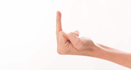 Side view of woman's middle finger over white background. Woman showing her aggressiveness and discontent.