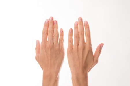 Two woman's hands are represented over white background. Woman showing her hands to demonstrate delicate skincare. 免版税图像