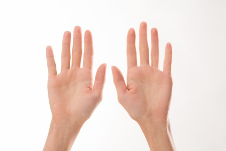 Two woman's palms represented over white background. Woman showing ten fingers that may help to overcross some difficulties.