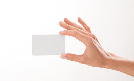 Womans hand holding a blank credit card over white background. Woman has a desire to demonstrate something on it. Stock Photo