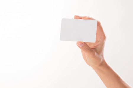 Woman holding credit card over white bacground in her right hand. Beautiful hand of woman represented over white background. Archivio Fotografico