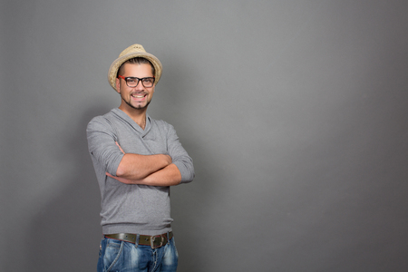 camera man: Fashionable hipster man posing with his arms crossed in studio. Smiling man in straw hat and glasses looking at the camera isolated in grey background. Stock Photo