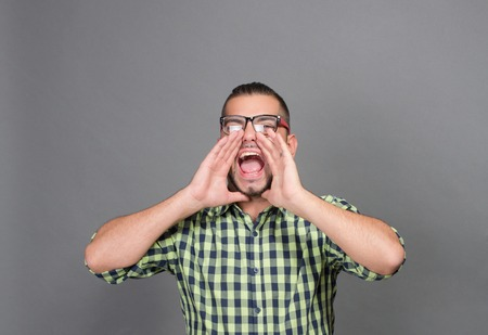 persuade: Fashionable hipster man screaming and shouting to someone in studio. Young man in glasses trying to persuade someone isolated on grey. Stock Photo