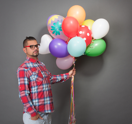 baloons: Handsome hipster man posing with multi-coloured baloons in studio. Young man in red shirt going to the birthday party.