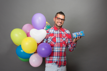 sexy funny: Handsome hipster man holding many multi-coloured baloons and a present in studio. Toothy smiling man in glasses going to the birthday party.