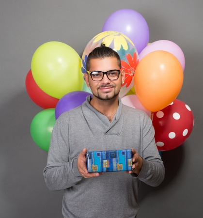 baloons: Handsome hipster man holding a present in front of him. Happy man in glasses looking at the camera, multi-coloured baloons are behind him.