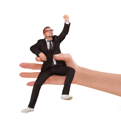 independance: Woman holding a businessman in her hand against white background. Man in glasses and business suit showing his independance. Stock Photo