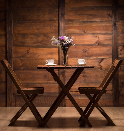 Beautiful wooden table for two persons to have a date in romantic atmosphere and drink a tasteful coffee or tea.