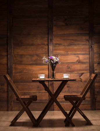Woooden table and two chairs represented in cafe or restaurant for spending evening with a cup of coffee or tea. 免版税图像