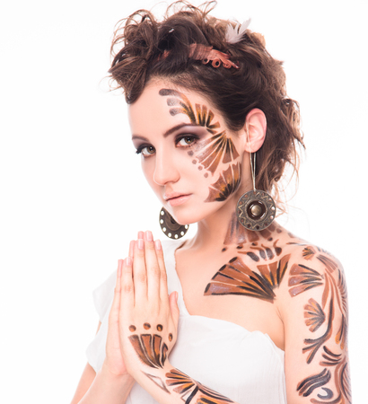 bodyart: Beautiful girl praying in the image of holiday elf. Pretty lady with fabulous bodyart clasped her hands in front of her isolated on white background.