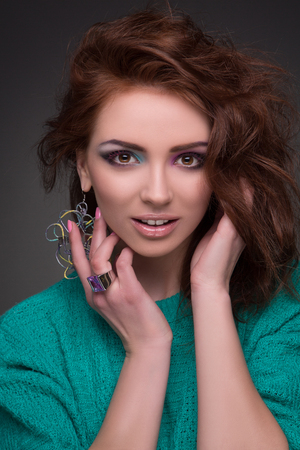 fashion magazine: Beautiful young girl with brown hair in green showing her creative make-up. Smiling lady posing for fashion magazine.