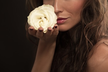 beautiful rose: Beautiful woman with elegant white rose isolated on black background. Ladys kisses are compared with rose petals.