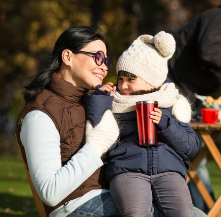 kid portrait: Mother and her daughter sitting all together and smiling. Mother in sunglasses smiling to her daughter while she is holding a cup of tea. Stock Photo