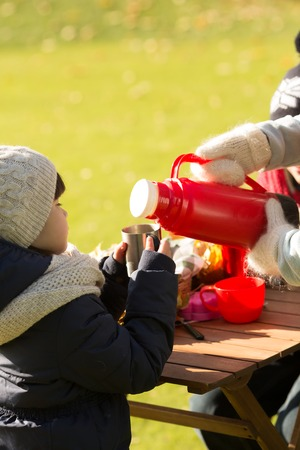 foe: A little kid holding a cup while her mother pouring hot tea. Little girl is waiting foe delicious warm tea while resting in the park on a picnic. Stock Photo