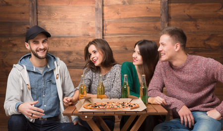 communicaton: Best friends resting in pizzeria and big excitedly smiling. Three friends looking at their happy friend in cap and waiting for his reaction.