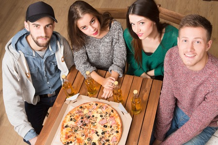 communicaton: Top view of happy company of best friends resting in pizzeria. Two men and two women looking at the camera and smiling for photographer.