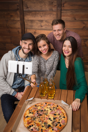making a save: Happy friends making top view selfies in pizzeria. Beautiful people trying to save best moments in best company of friends.