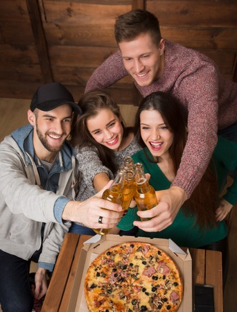 communicaton: Company of friends resting with alcohol drinks in pizzeria. People making cheers and happy smiling from excitement.