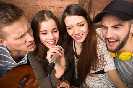 karaoke: Happy friends spending their free time singing songs in karaoke. Beautiful people holding microphone in front of them. Stock Photo