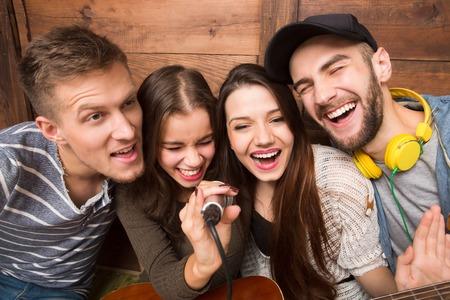 cantando: Dos hombres y dos mujeres que pasan su tiempo libre en el karaoke. La gente moderna que cantan canciones y feliz sonriendo para la cámara. Foto de archivo