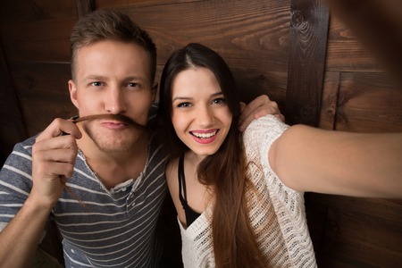 Selfie project. Young couple posing for mobile phone's camera. Handsome man and woman mankig selfies isolated on wooden background. 스톡 콘텐츠