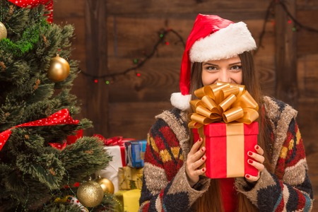 christmas greeting: Beautiful girl holding a Christmas present in front of her. Happy woman in Santa hat standing near New Year tree and waiting for celebration.