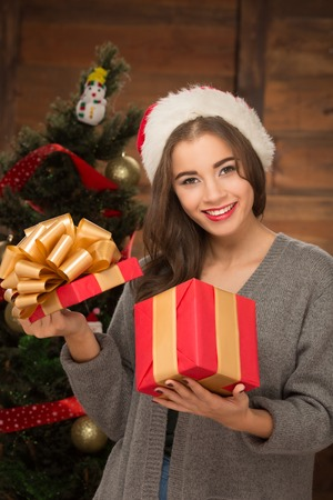 holiday spending: Portrait of beautiful and attractive girl opening a present near New Year tree. Smiling lady spending Christmas holiday at home.