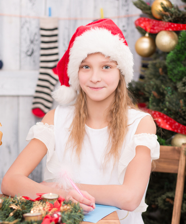 post card: Portrait of beautiful girl in Santa Clauses hat sitting at the table and writing New Year and Christmas congratulation in the post card.