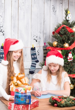 post card: Happy lady standing near table and looking at her sister writing New Year and Christmas congratulation on the post card. Stock Photo