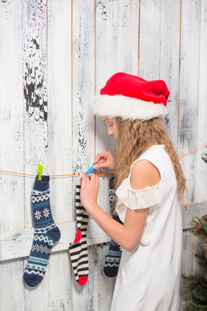 clauses: Teenage girl in Santa hat hanging New Year and Christmas socks for Santa Clauses presents or gifts.