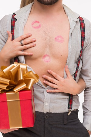 lustful: Close-up portrait of mans body with many kisses. Man holding a present while his girl-friend touching his body.