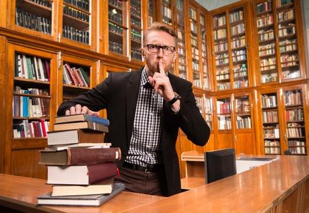 Il y a beaucoup de livres prises par l'homme bibliothécaire pour les donner aux étudiants. Homme montrant signe calme.