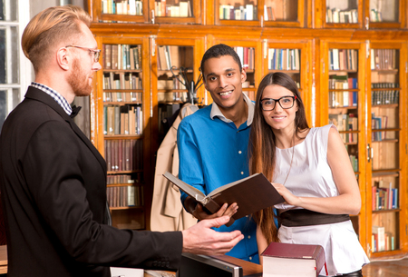 new books: Librarian man showing students new books in library. Happy students smiling and they are going to study. Stock Photo