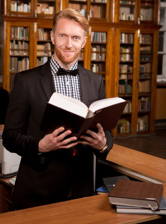 librarian: Portrait of real librarian holding a heavy book in library. Handsome man in black suit smiling for the camera.