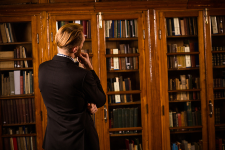 periodicals: Close-up portrait of young business man in black suit reading, perusing books, magazines and periodicals in library.