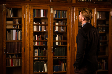 periodicals: Photo of young handsome man in black suit searching books, magazines and periodicals in library.