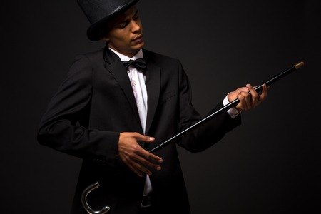 imagining: Portrait of handsome man in top hat holding cane and dreaming or imagining that he is playing the guitar.
