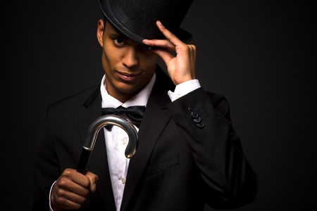 Close-up portrait of handsome man adjusting black top hat. Attractive asian man in black business suit posing with cane.