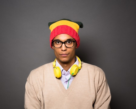 looking directly at camera: Head and shoulders portrait of hipster brazilian man in studio. Attractive man with earphones looking directly at the camera. Stock Photo