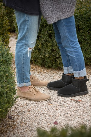 striding: Low view of legs of man and woman standing face to face. People both in the blue jeans hugging in the autumn park. Stock Photo