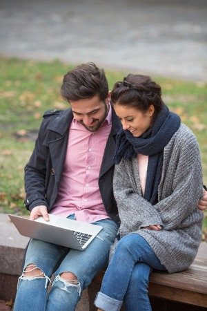 astonishing: Happy couple surfing the Internet in the autumn city. Handsome man trying to show his girl-friend something exciting and astonishing.
