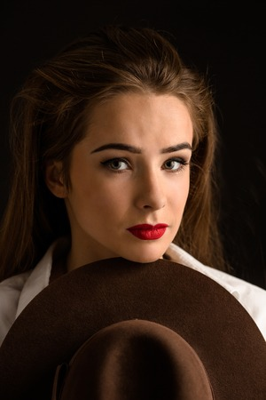 looking directly at camera: Beautiful model lady with red lips posing with hat in studio. Portrait of elegant woman looking directly at the camera.