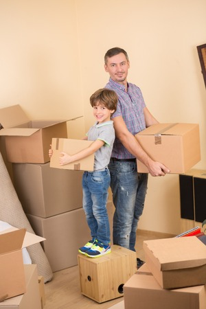 heave: Moving, home and family concepts. Smiling couple of father and son holding heave boxes or cardboards in a new house.