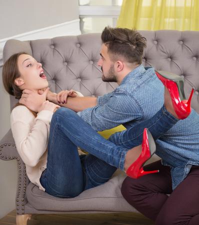 Coppie alla psicoterapeuta aver combattere. Bel uomo cercando di strangolare la moglie sul divano.