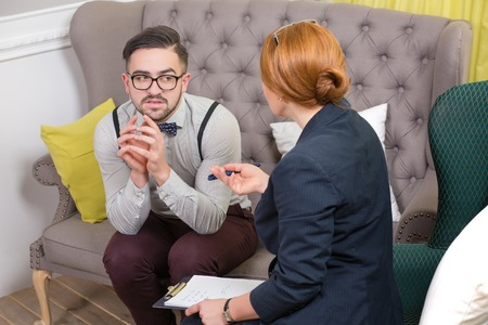 cliche: A female psychotherapist treats a teenage male patient with normal and cliche ways while he is sitting on the sofa. Stock Photo