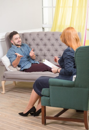 gesticulating: Portrait of gesticulating man talking with psychologist. Handsome man reclining comfortably on a couch talking to his psychiatrist. Stock Photo