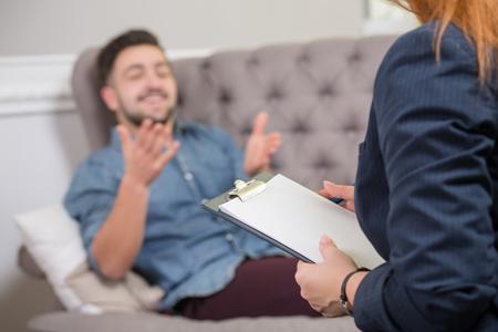 terapia psicologica: Primer plano retrato de psiquiatra haciendo notas femeninas en frente del paciente durante la sesión de terapia psicológica.