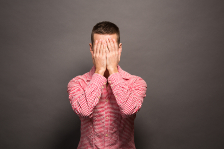 one eye: Shocking news. Portrait of shocked young man looking at camera and covering his face while standing over grey background.