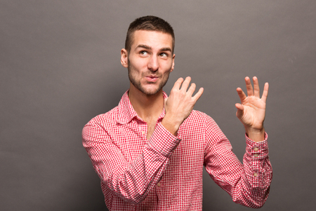 professional flute: Young brunette man as if playing block flute and looking away in studio. Handsome man in pink shirt is a professional musician.